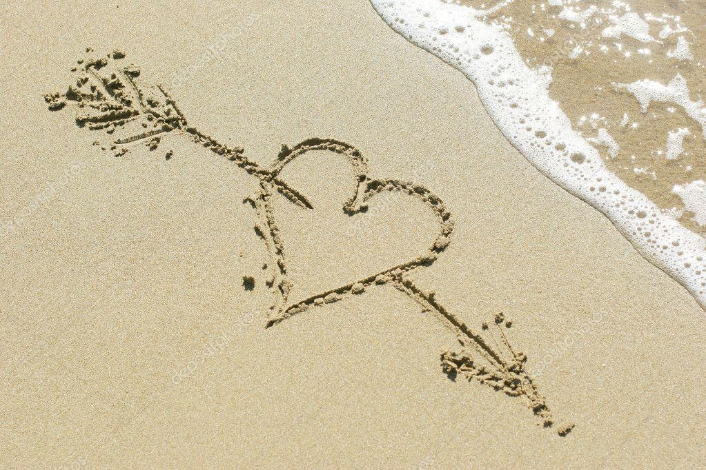Heart pierced by Cupid's arrow drawn in the sand
