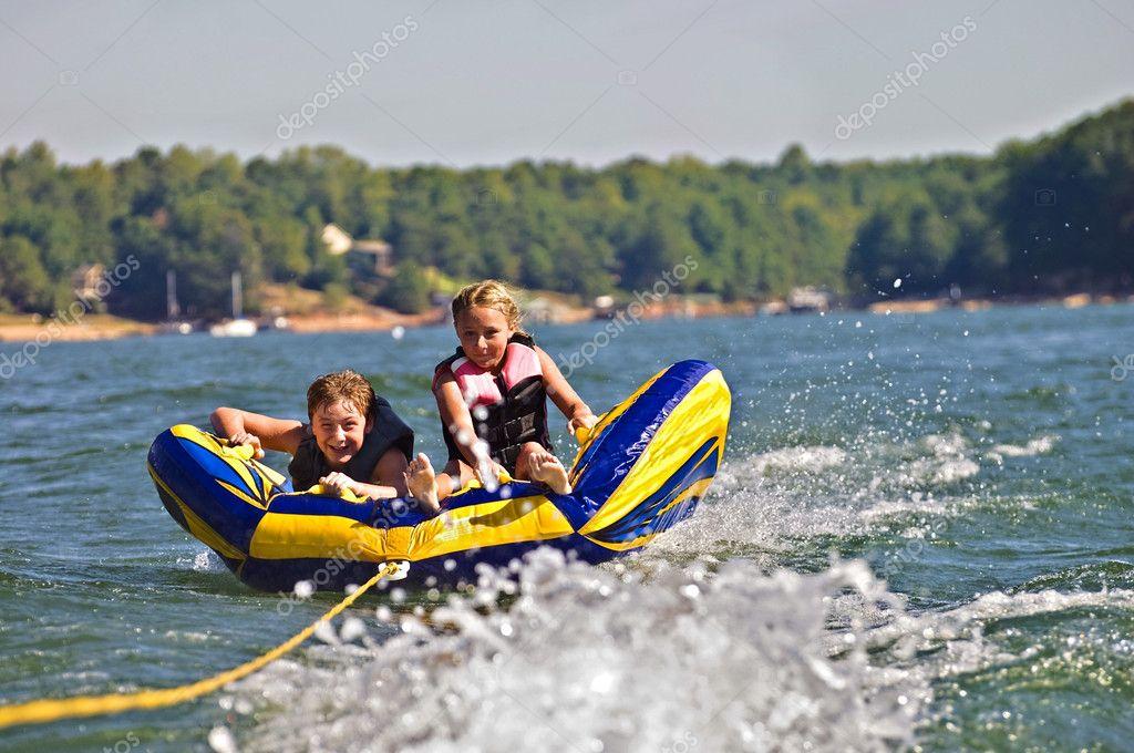 Ragazzo e ragazza tubi dietro barca