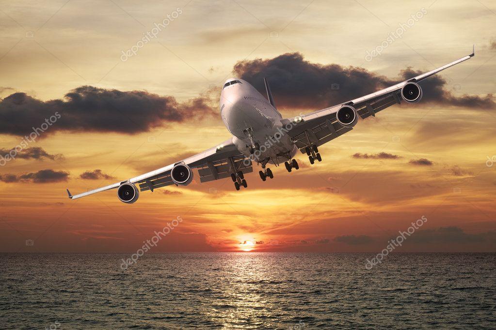 Evening flight. Jet plane over the sea at sunset.
