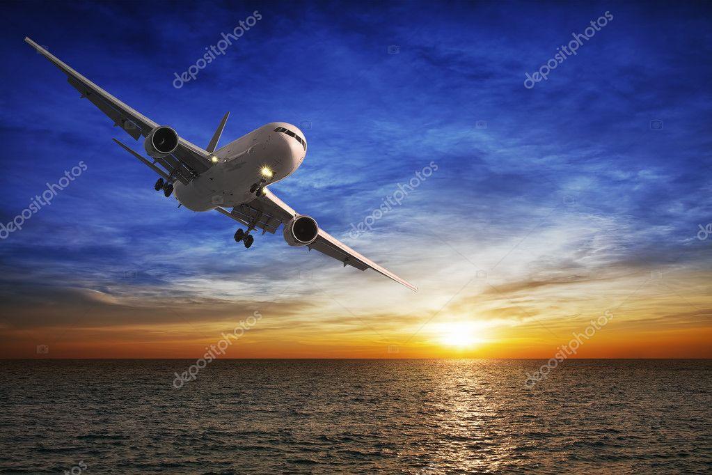 Night flight. Jet aircraft over the sea at dusk.