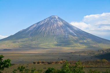 Ol Doinyo Lengai volcano and Maasai village in Tanzania