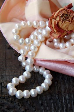 White pearls in a pink bag with dry rose