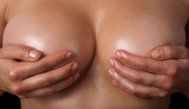 Topless woman body covering her breast with hand