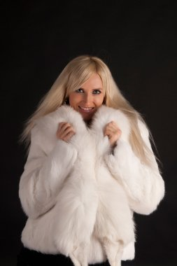The glamour blonde in a warm white fur coat