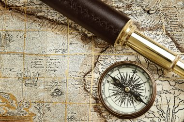 Vintage brass telescope and compass at old map