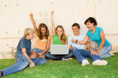 Group of teens with laptop hands raised for success or winning