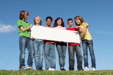 Group of diverse children holding blank white poster
