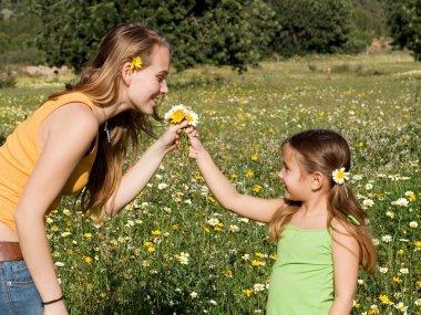 Kid giving flower to mum