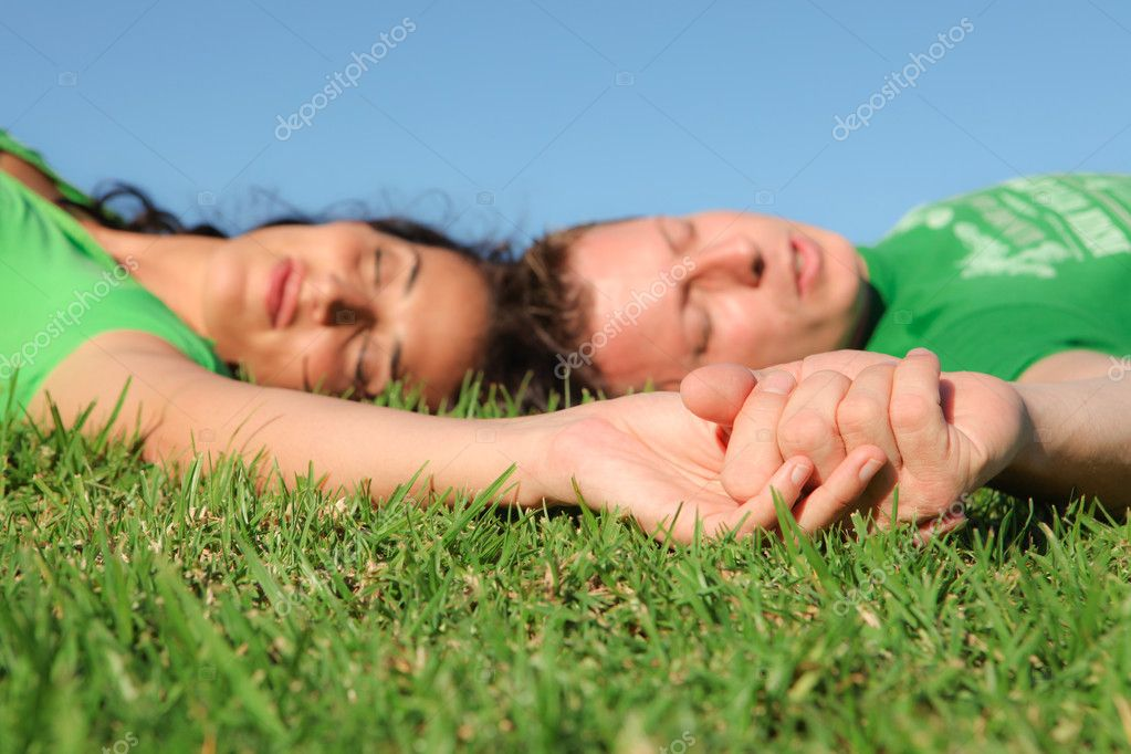 Sleeping couple , focus on holding hands,