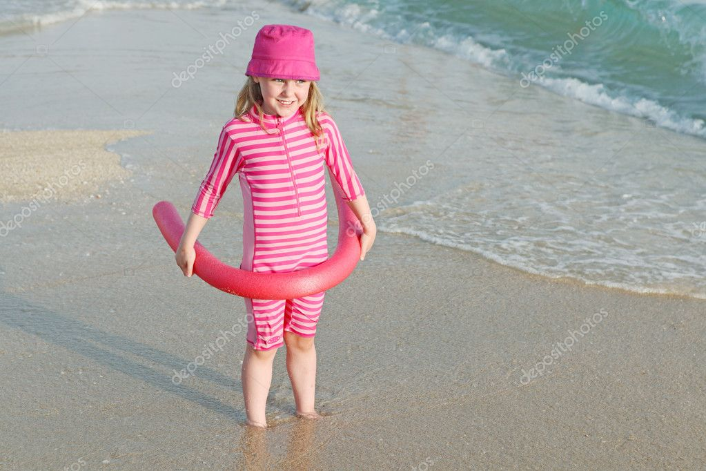 Young child on beach vacation with sun protection suit and hat.