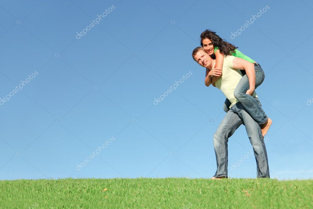 Happy smiling couple outside on grass giving piggy back