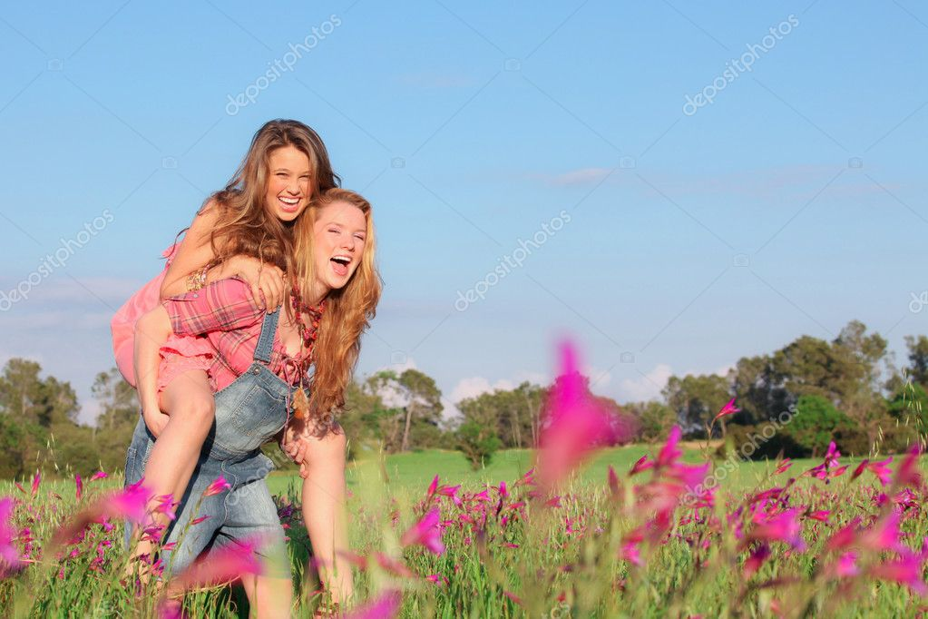 Happy smiling spring or summer piggy back teens or teenagers