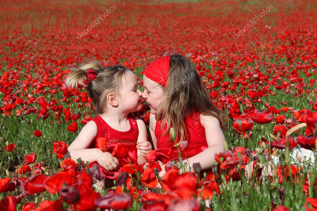 Little girls sitting in summer poppy field
