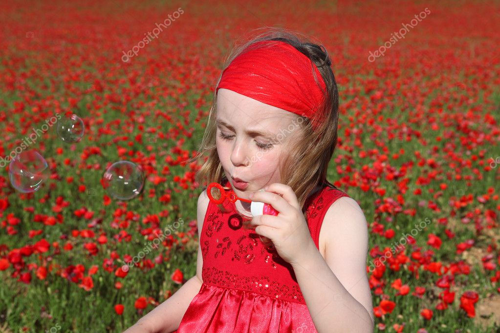 Little girl blowing bubbles playing outdoors in summer