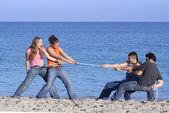 Fotografie Tauziehen, Teens spielen am Strand im Sommerurlaub oder Frühlingsferien