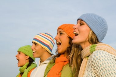 Group of carolers or carol singers singing or sports spectators cheering