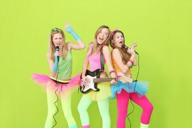 Girl band, group of girls singing and playing guitar