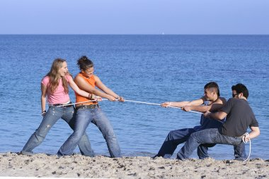 Tug of war, teens playing on beach on summer vacation or spring break