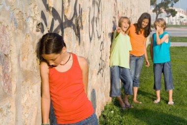 School bully or bullies bullying sad lonely child