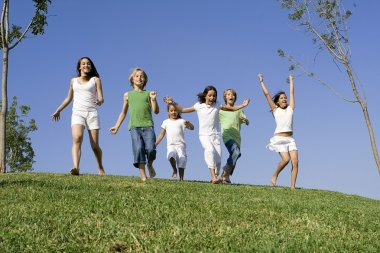Group of happy kids at summer camp or school running or racing