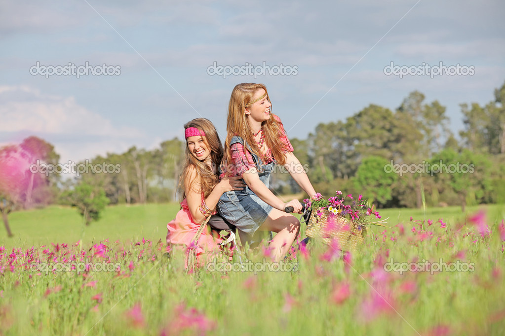 Happy girls riding bike or bicycle in summer meadow