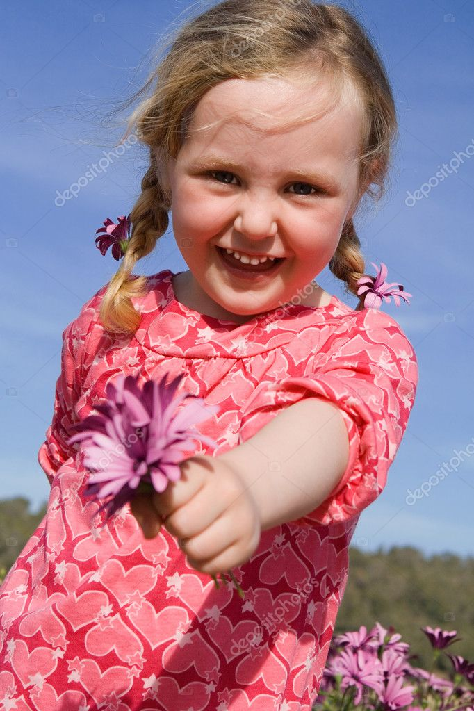 Happy summer kid giving gift of flower