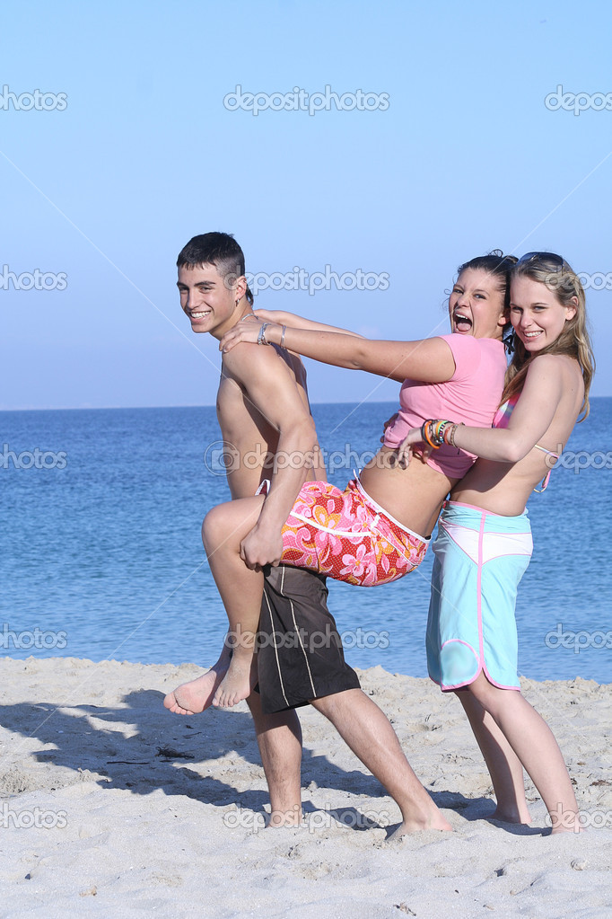 Kids goofing on beach on summer vacation or spring, break