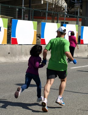 Dad and daughter are running at the finish of the Marathon