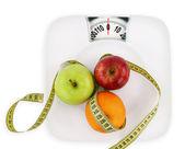Fotografie pojem dieta. ovoce s měřicí pásku na talíři jako váha