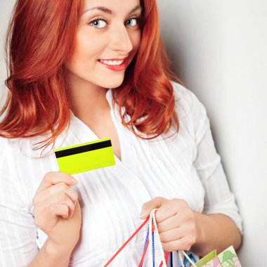 Shopping woman with credit card against wall