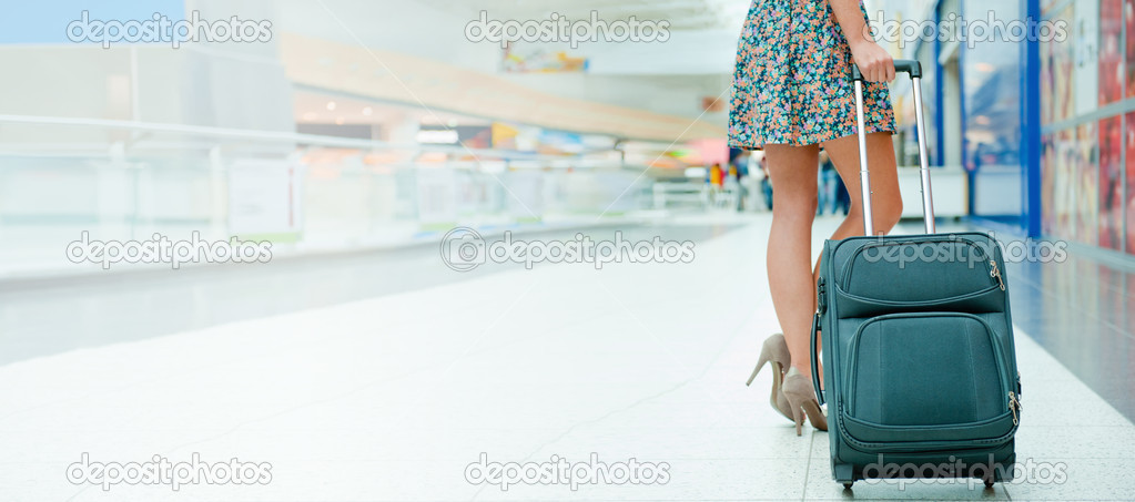 Woman's legs and travel suitcase at international airport tax fr