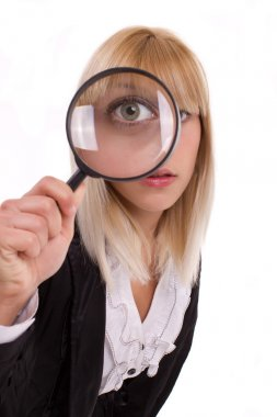 Close-up woman looking through magnifying glass