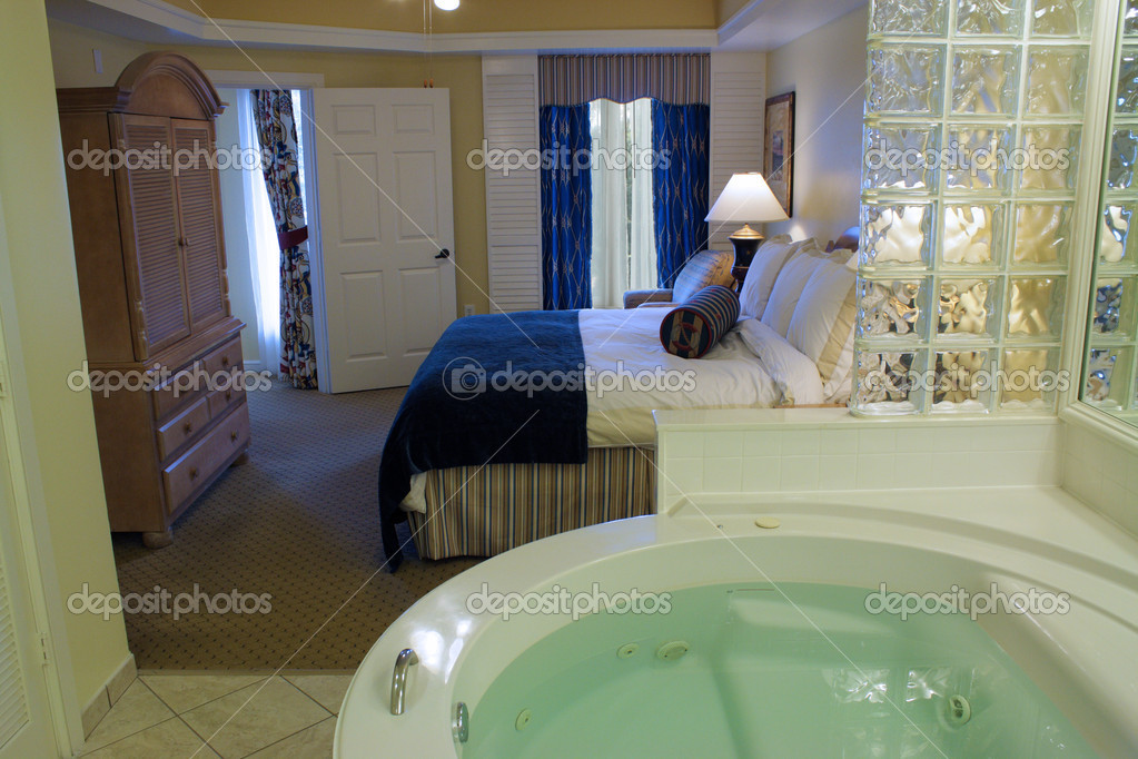 A Large Filled Jacuzzi Tub In The Foreground... A Master Bedroom In The  Background. U2014 Photo By Csproductions