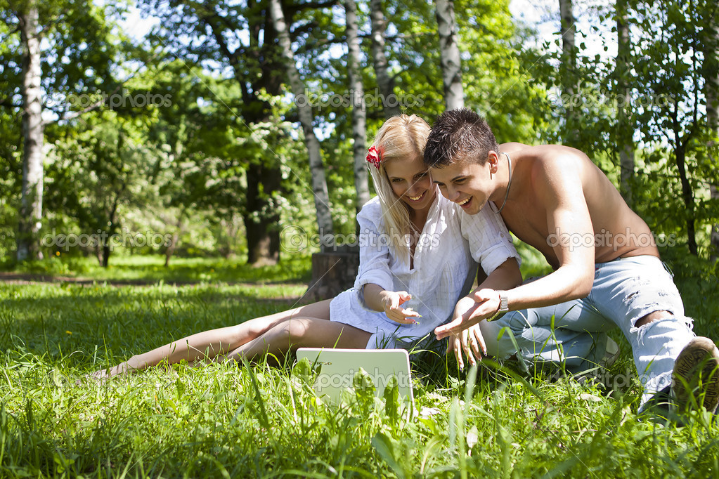 Couple using a laptop outdoors and looking happy