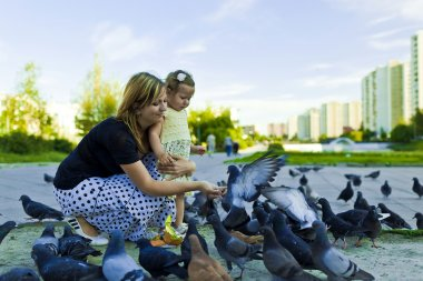 Little girl and mother feeding pigeons urban blue-gray