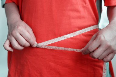 Fat woman measuring waist