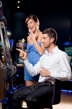 Young couple winning at the slot machine
