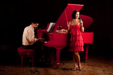 Man playing the piano and woman singing