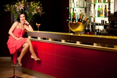 Woman red dress at bar counter smiling