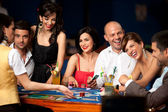 Fotografie směje se přátelé hrací karty v kasinu