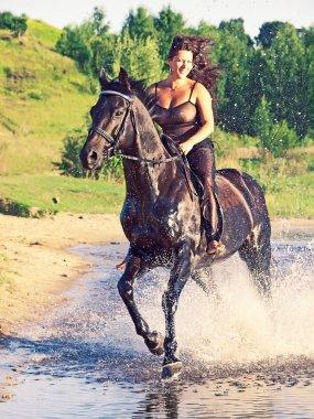 Sexy women galloping on horse at lake