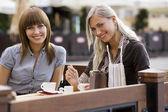 Fotografia due giovani sorridente signora in café