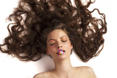 Sweet model posing with closed eyes wearing candy make up