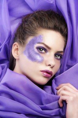 Young girl laying on purple fabric wearing glitter make up