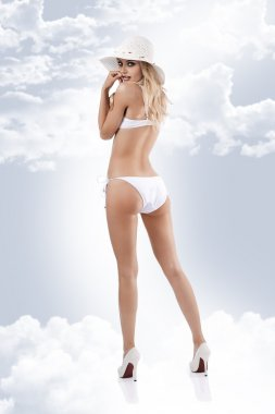 Young girl posing with a white bikini and a white summer straw h