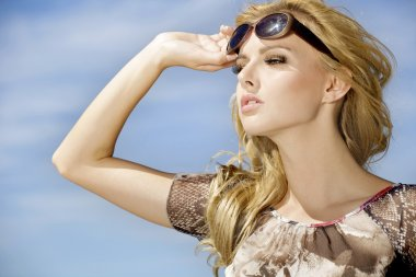 Portrait of beautiful blonde girl in sunglasses on background blue sky stock vector