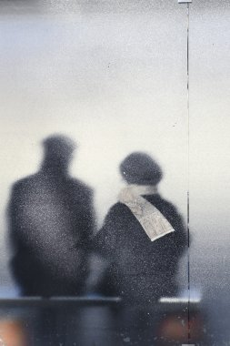 Old age - old couple sitting in a bus stop (color toned image)