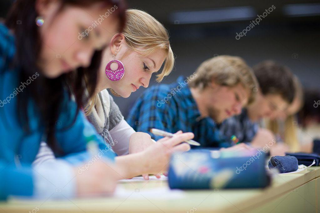 Pretty female college student sitting in a classroom full of stu