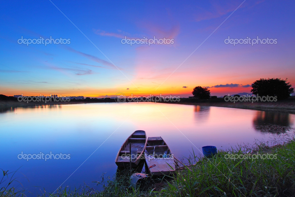 Sunset along the pond with two boats and two magical color on sk