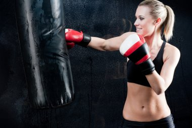 Boxing training woman punching bag in gym
